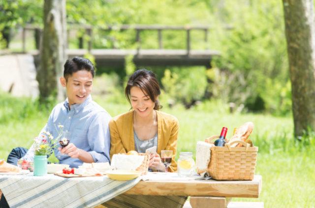 ピクニックデートで持ち物を並べるカップル