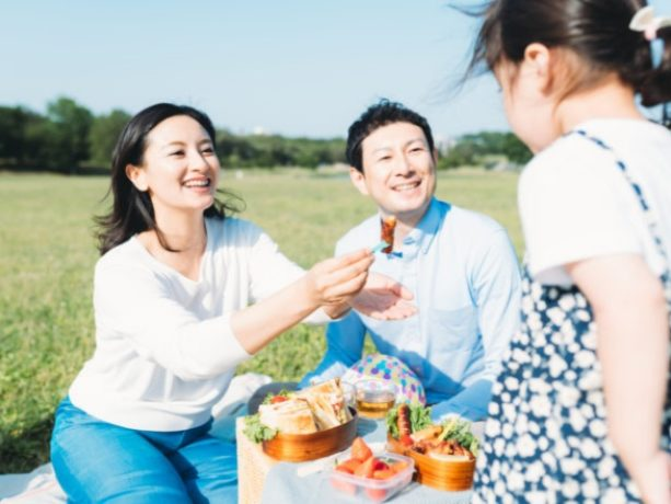 お弁当箱を持ってピクニックをする家族